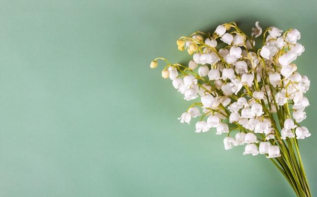 Blumenstrauß der maiglöckchen auf dem grünen hintergrund. draufsicht, flach liegen mit platz für text