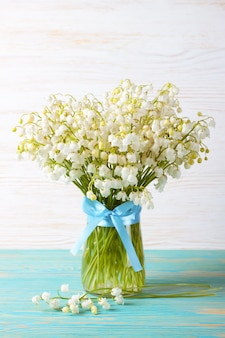 Blumenstrauß der maiglöckchen in einer vase mit blauem band auf einem blauen und weißen hölzernen hintergrund