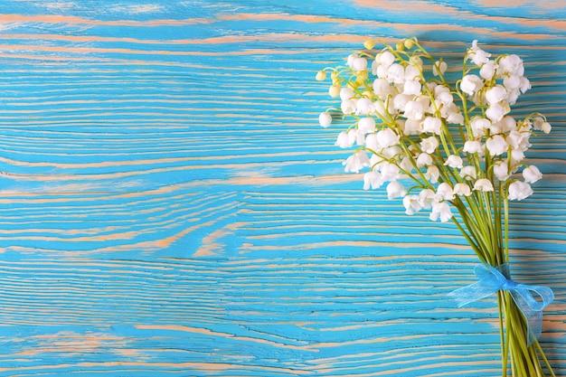 Blumenstrauß der maiglöckchen mit blauem bogen auf dem blauen hölzernen hintergrund. draufsicht, flach liegen.