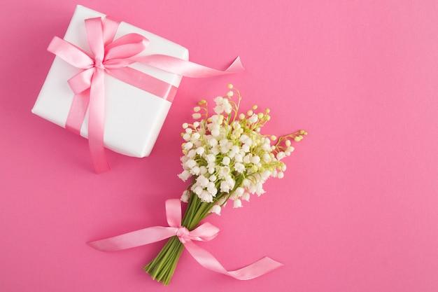 Blumenstrauß der maiglöckchen mit rosa schleife und weißer geschenkbox auf dem rosa tisch. draufsicht. speicherplatz kopieren.