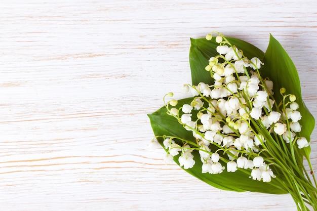 Blumenstrauß der maiglöckchenblumen auf weinlesetafel weißem holztisch. horizontale flache lage, draufsicht.