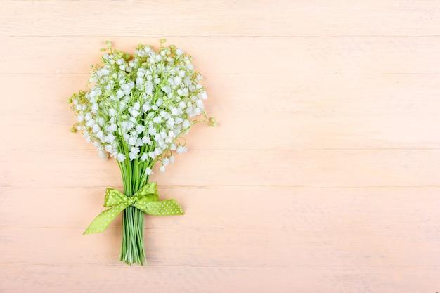 Blumenstrauß der maiglöckchenblumen mit einer grünen schleife auf einem hölzernen rosa hintergrund mit einem kopienraum