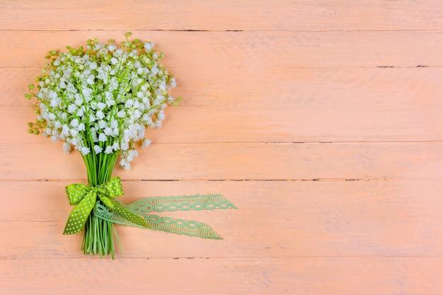 Blumenstrauß der maiglöckchenblumen mit einer schleife und einem band auf einem hölzernen rosa hintergrund mit einem kopienraum