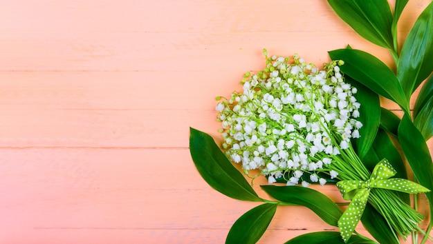 Blumenstrauß der maiglöckchenblumen mit grünen blättern mit einer schleife auf einem hölzernen rosa hintergrund mit einem kopienraum