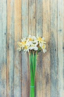 Blumenstrauß der narzissenblumen auf hölzernem retro-schmutz-nahaufnahme