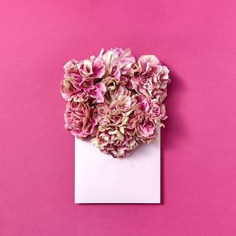 Blumenstrauß der nelken in einem handgefertigten umschlag auf einem magentafarbenen hintergrund mit kopienraum. flach liegen.