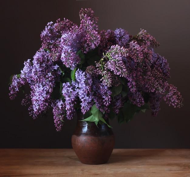 Blumenstrauß der purpurroten flieder in einem lehmkrug auf dem tisch. stillleben mit blumen.