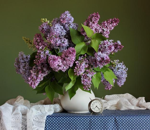 Blumenstrauß der purpurroten flieder in einem weißen krug.