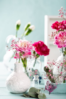 Blumenstrauß der rosa nelke in der glasvase auf heller türkisfarbener holzoberfläche. muttertag, geburtstagsgrußkarte. speicherplatz kopieren