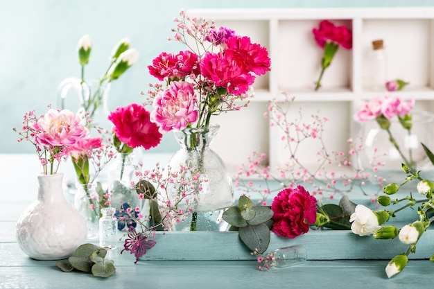 Blumenstrauß der rosa nelke in der glasvase auf heller türkisfarbener holzoberfläche. muttertag, geburtstagsgrußkarte