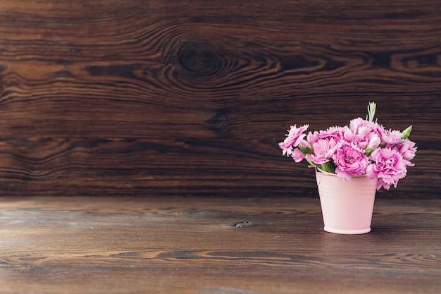 Blumenstrauß der rosa nelkenblumen in der vase auf holz. leerraum für text