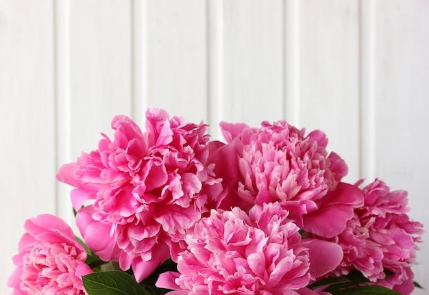 Blumenstrauß der rosa pfingstrosen auf einem hellen bretthintergrund.