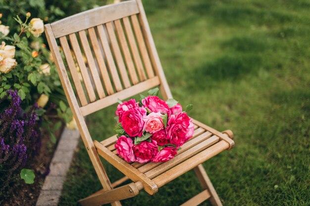 Blumenstrauß der rosa rosen auf holzstuhl