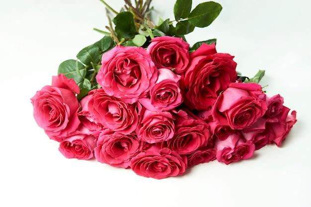 Blumenstrauß der rosa rosen auf weißem hintergrund mit kopienraum.