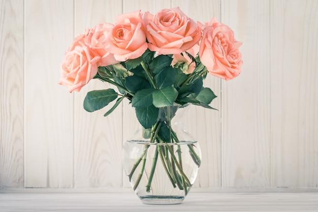 Blumenstrauß der rosa rosen in einer vase auf einer hölzernen brettwand. stillleben, geschenkkarte