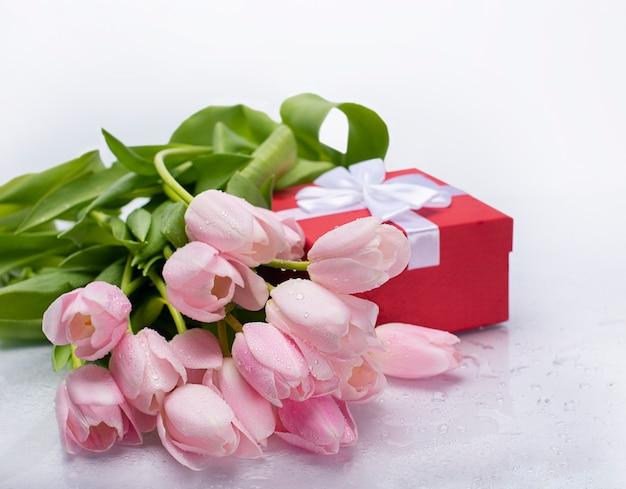 Blumenstrauß der rosa tulpen und einer roten box mit einem geschenk auf einem weißen isolierten hintergrund