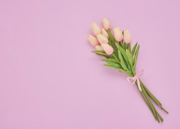 Blumenstrauß der rosa tulpenblumen auf einem rosa hintergrund