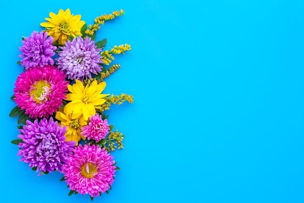 Blumenstrauß der rosa und gelben blumen auf einem blauen hintergrund. modell mit kopierplatz.