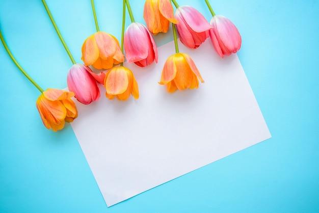 Blumenstrauß der rosa und orange tulpen und ein stück papier auf einem blauen hintergrund