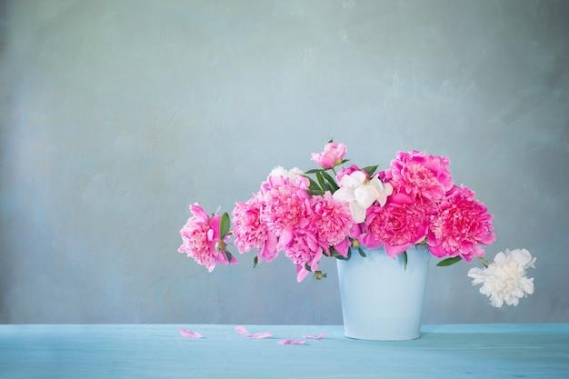 Blumenstrauß der rosa und weißen pfingstrosen auf der alten tischwand