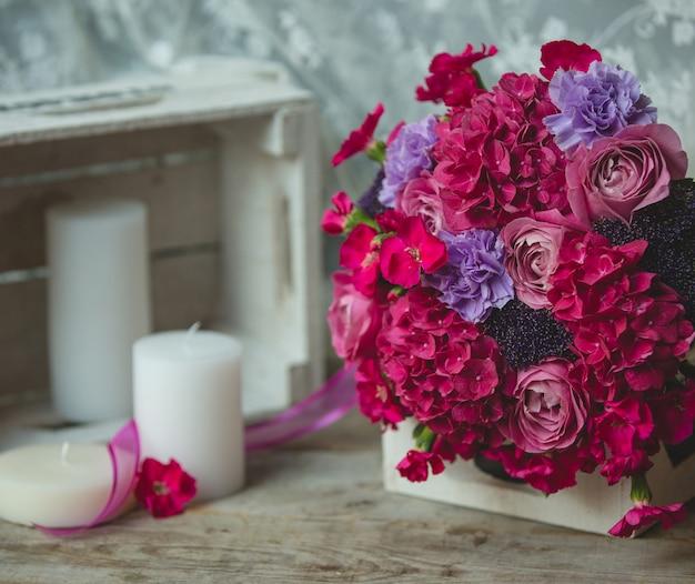 Blumenstrauß der roten blume, der herum auf einem buch und kerzen auf einer tabelle steht