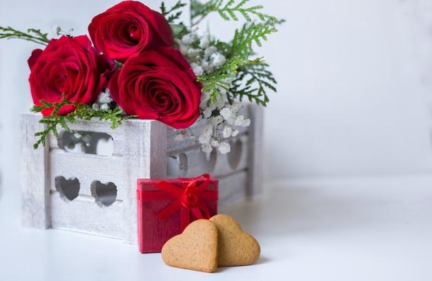 Blumenstrauß der roten rosen mit einem geschenk und herzen formte plätzchen