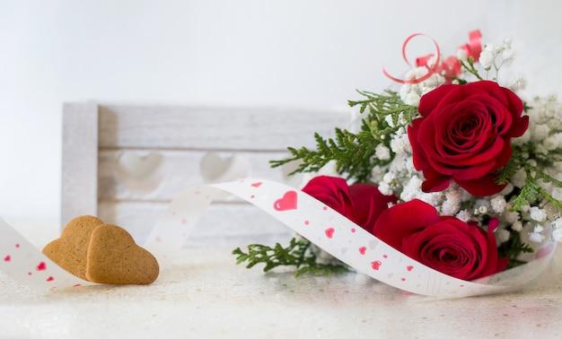 Blumenstrauß der roten rosen mit geformtem plätzchenhintergrund des herzens