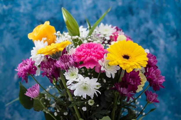 Blumenstrauß der schönen blumen mit blauem hintergrund