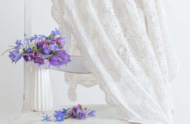 Blumenstrauß der schönen frühlingsviolettblumen auf weißer oberfläche