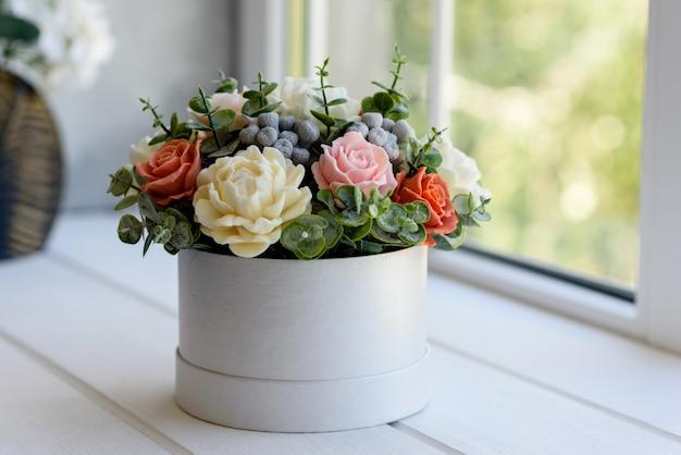 Blumenstrauß der schönen hellen rosenblumen in einem geschenk zylindrischen pappkarton