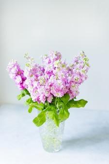 Blumenstrauß der schönen lila mattiola in der kristallvase auf tisch.