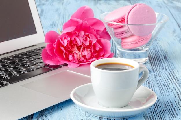 Blumenstrauß der schönen pfingstrosen, tasse mit kaffee und computer auf leuchttisch