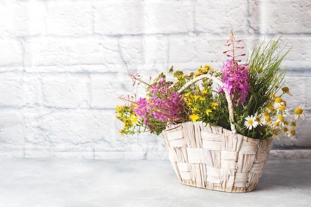 Blumenstrauß der schönen wildblumen in einem korb auf einem grauen hintergrund mit kopienraum.