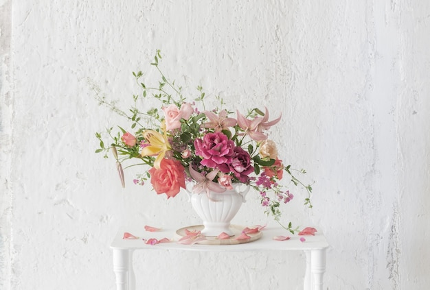 Blumenstrauß der sommerblumen in der vase auf weinleseweißholzregal auf weißem hintergrund