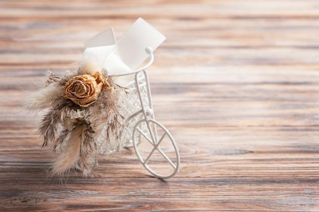 Blumenstrauß der trockenen blumen auf dekorativem fahrrad auf rustikalem tisch. grußkarte für hochzeit oder urlaub in natürlichen tönen