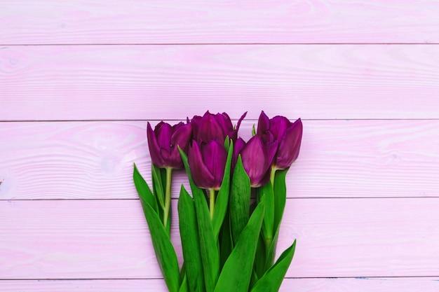 Blumenstrauß der tulpe blüht auf rosafarbenem holz mit exemplarplatz