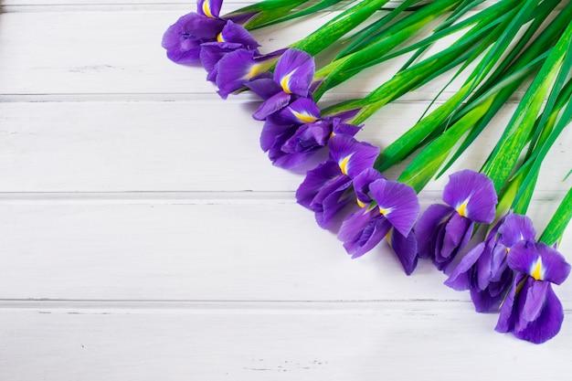 Blumenstrauß der violetten iris auf hölzernem weißem hintergrund
