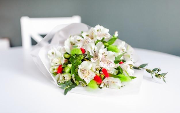 Blumenstrauß der weißen alstroemeria blüht auf einem weißen runden tisch liegend.