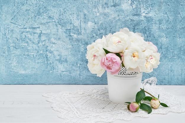 Blumenstrauß der weißen pfingstrosen im weißen vase. urlaub, exemplar