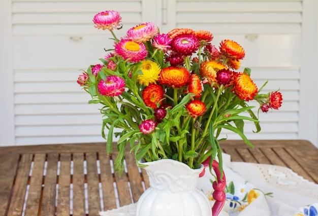 Blumenstrauß des ewigen blumenstraußes in der vase auf hölzernem gartentisch