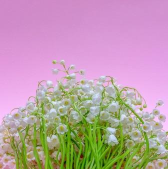 Blumenstrauß des maiglöckchens blüht auf einem hellrosa hintergrund