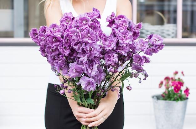 Blumenstrauß des purpurroten lila rittersporns in den händen der frauen auf der straße