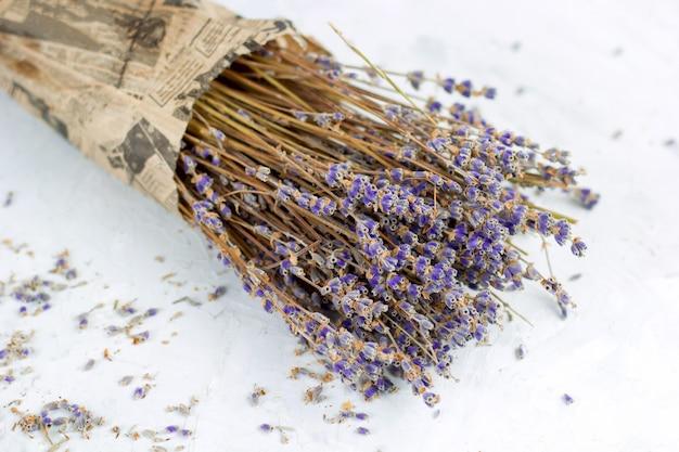 Blumenstrauß des trockenen lavendels blüht im packpapier auf draufsicht des weißen schäbigen hintergrundes