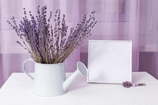 Blumenstrauß des trockenen lavendels in der gießkanne mit bilderrahmenmodell über fenster auf weißer tabelle. weicher fokus.