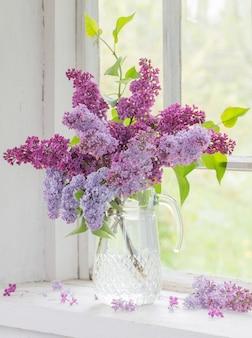 Blumenstrauß flieder in einem glaskrug auf altem weißem fensterbrett