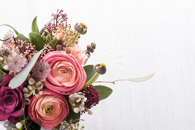 Blumenstrauß im zinnbecher auf hellem hintergrund