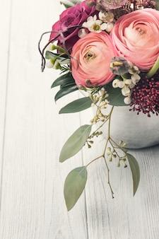 Blumenstrauß im zinnbecher auf licht