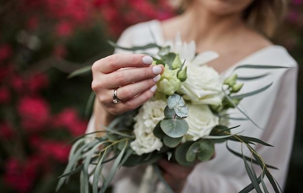 Blumenstrauß in den händen der braut, frau, die sich vor der hochzeitszeremonie fertig macht