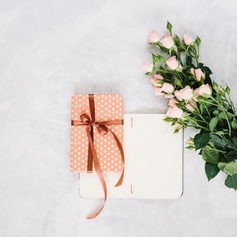 Blumenstrauß in der nähe von gegenwart und offenes notizbuch