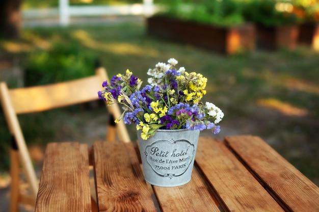 Blumenstrauß in der weinlesevase auf holztisch im garten